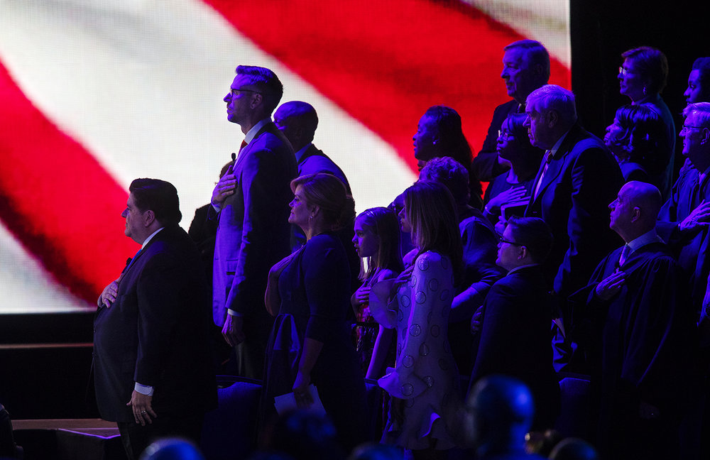 Governor-elect J.B. Pritzker and other office holders and their guests stand for the playing of the national anthem during the Illinois Inaugural Ceremony at the Bank of Springfield Center Monday, Jan. 14, 2019. [Ted Schurter/The State Journal-Register]