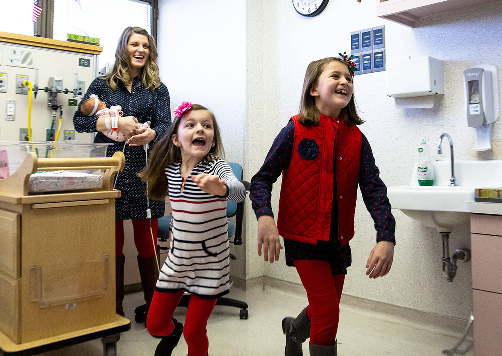 It was a joyful surprise for Addisyn Shanle, 7, left, and her sister Brookelyn, 9, when their dad, Chief Warrant Officer II Dustin Shanle, walked into the room to see the newest member of their family Tuesday, Jan. 8, 2019 at HSHS St. John's Children's Hospital in Springfield, Ill. Danielle Shanle, who is holding their newborn daughter, Callie, and was in on the plan, gave birth almost two months early while Dustin was deployed with the Marines in Afghanistan. [Rich Saal/The State Journal-Register]
