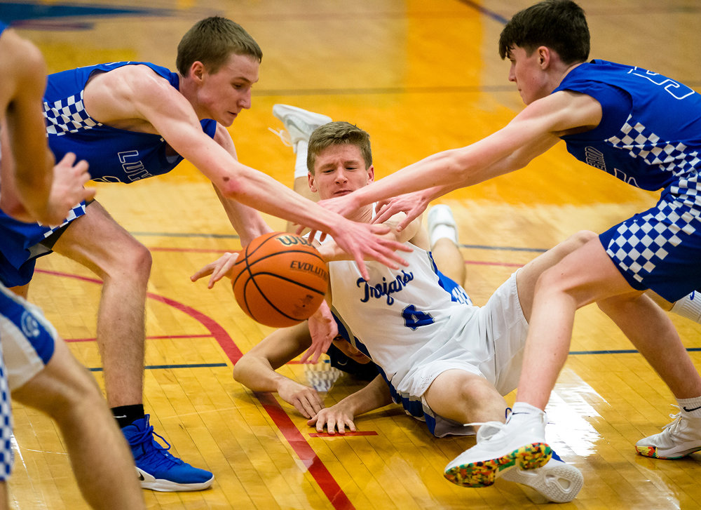 Auburn's Reece Conway (4) tries to clear a pass between two Lutheran defenders after hitting the floor in the first half during the opening night of the Boys Sangamon County Basketball Tournament at Lincoln Land Community College's Cass Gymnasium , Monday, Jan. 7, 2019, in Springfield, Ill. [Justin L. Fowler/The State Journal-Register]