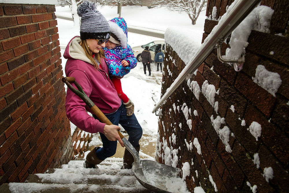 Morgan Miller carries her one-year-old daughter Mia Jennings as she shovels the stairs to her Springfield home Sunday, Jan. 13, 2019. Miller said she's learned how to do a lot of things while holding a baby in the last year. [Ted Schurter/The State Journal-Register]