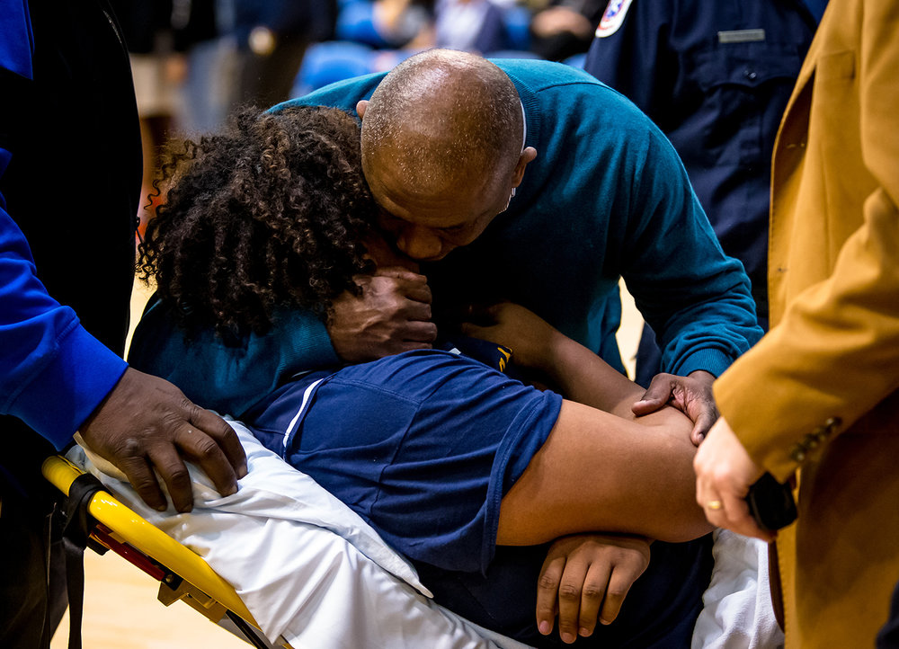 Southeast boys basketball head coach Lawrence Thomas hugs Southeast's Herb McMath (41) as he is taken off the court on a stretcher after being injured in the second quarter on opening night of the Boys City Tournament at the Bank of Springfield Center, Wednesday, Jan. 16, 2019, in Springfield, Ill. [Justin L. Fowler/The State Journal-Register]