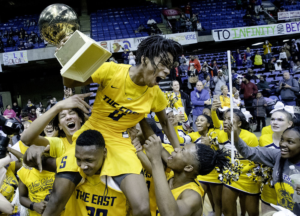Southeast's Terrion Murdix lets out a celebratory roar as he hoists the championship trophy after the Spartans defeated Sacred-Heart Griffin 84-50 during the Boys City Tournament at the Bank of Springfield Center Friday, Jan. 18, 2019.  [Ted Schurter/The State Journal-Register]