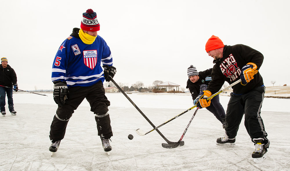 Undeterred by the below freezing temperatures, Joel Johnson, left, Derrick Brown, Bryan Adams and Jeff Ryan cleared snow off the pond at Southwind Park in Springfield to play ice hockey Saturday, Jan. 26, 2019. Johnson said said they enjoy taking advantage of the outdoor venue that slows the game down and requires more puck control compared to playing inside with backgrounds that corral errant shots. [Ted Schurter/The State Journal-Register]