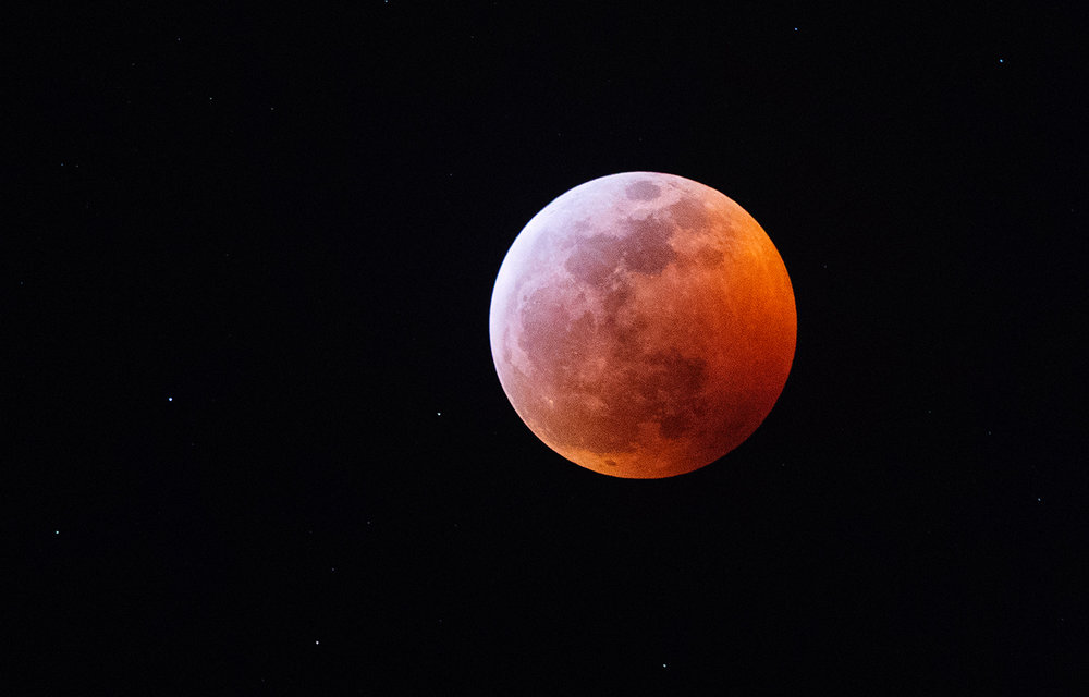"The shadow of the earth darkens the surface of the moon during a total lunar eclipse Sunday, Jan. 20, 2019. The eclipse coincided with a ""supermoon,"" when the moon is closer to earth than normal, and is also called a ""blood moon"" due to the color imparted by the eclipse. [Ted Schurter/The State Journal-Register]"