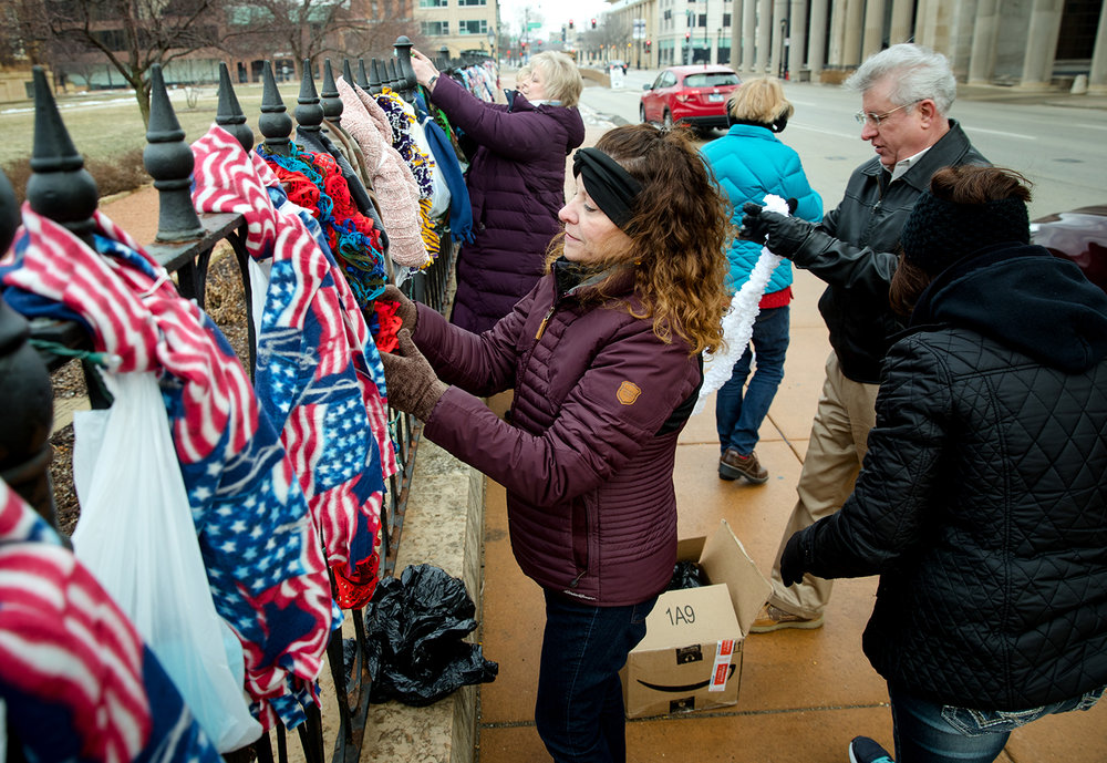 Ann Randol helps place winter scarves on the fence surrounding the Old State Capitol Saturday, Feb. 2, 2019. The effort to distribute the free cold weather apparel was organized by Scarves for Springfield which planned to distribute any items remaining at the end of the day to social service organizations that assist the homeless. [Ted Schurter/The State Journal-Register]