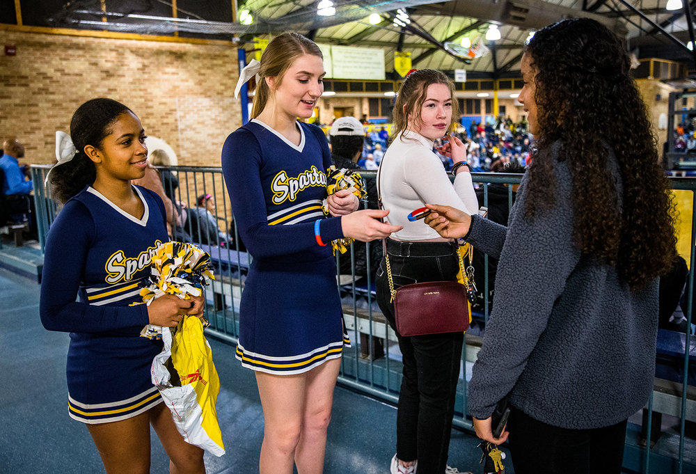 Southeast senior cheerleader Gianna Flammini, center, and junior cheerleader Paige Price hand out unity bracelets to students prior to Southeast taking on Springfield at Southeast High School, Tuesday, Feb. 5, 2019, in Springfield, Ill. Students of the Mayor's Youth Council created the rubber bracelets that spelled out #unityinourcommunity, in the city's school colors blending together to combat hateful comments made toward Southeast High School students about winning the Spirit Award. [Justin L. Fowler/The State Journal-Register]