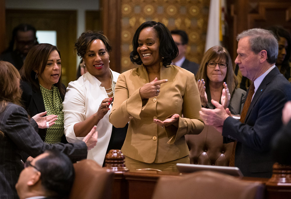 Illinois State Sen. Kimberly Lightford, D-Maywood, center, is applauded by Illinois State Sen. Iris Martinez, D-Chicago, left, Illinois State Sen. Toi Hutchinson, D-Olympia Fields, and Illinois Senate President John Cullerton, D-Chicago, right, after Senate Bill 1, a bill she sponsored to raise the state's minimum wage to $15 an hour by 2025, passed the Illinois Senate with a vote of 39-18 at the Illinois State Capitol, Thursday, Feb. 7, 2019, in Springfield, Ill. [Justin L. Fowler/The State Journal-Register]