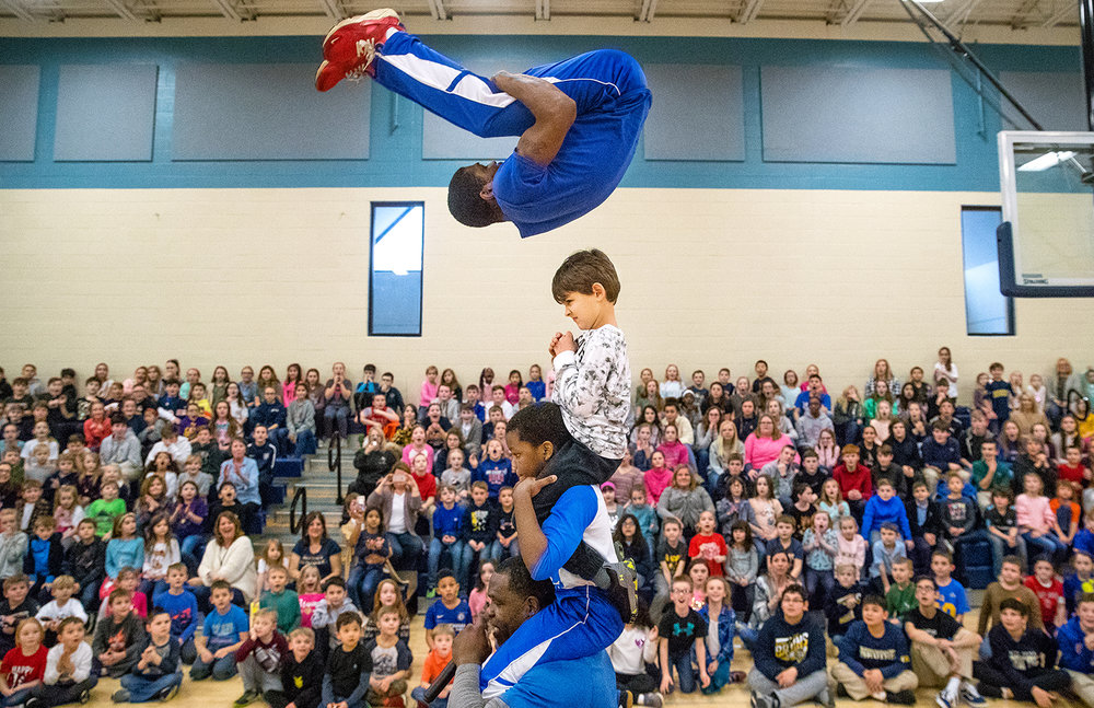 """Blessed Sacrament School kindergartener Tyler Smith, sitting on the shoulders of nine-year-old Julius Davis who is sitting on the shoulders of Coach Tim Shaw, reacts as Elijah Newbern flies inches over his head during a performance by The Chicago Boyz Acrobatic Team at the school Thursday, Feb. 7, 2019. The mission of the travelling team, recently featured on the NBC show """"America's Got Talent,"""" is to provide at risk youth from the inner city with an opportunity to better their lives through education, cultural enrichment and increased self-esteem. [Ted Schurter/The State Journal-Register]"""
