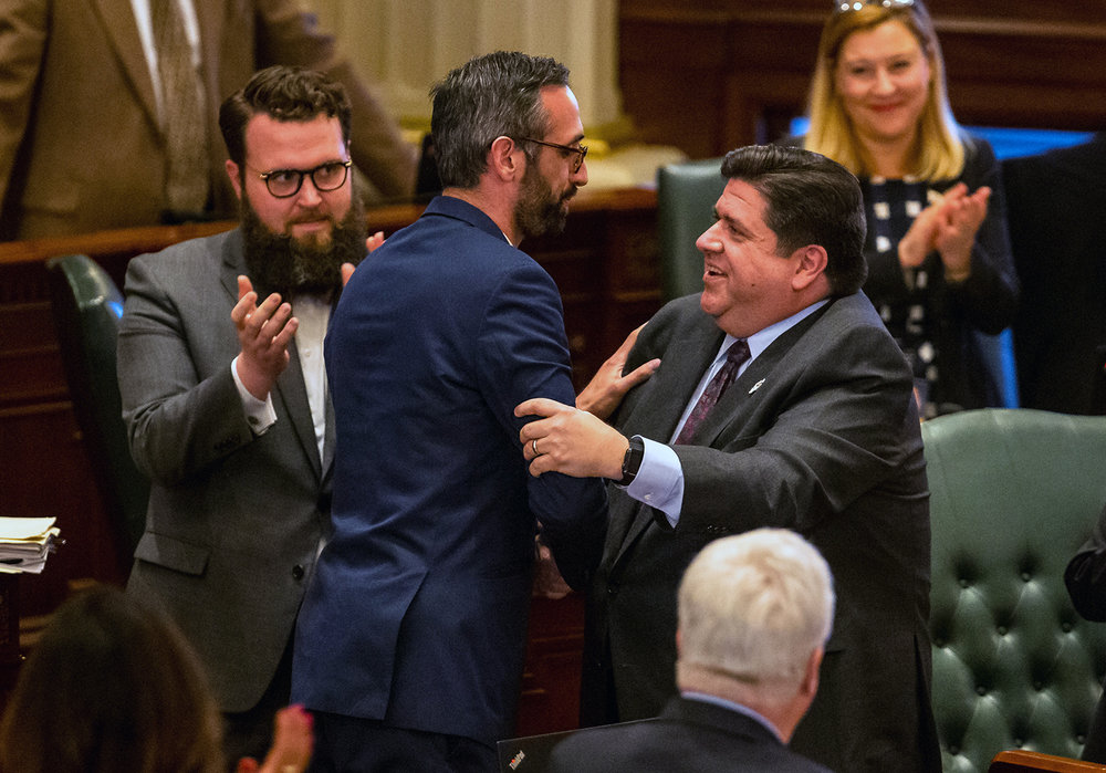 Illinois Governor JB Pritzker, right, congratulates Illinois State Rep. Will Guzzardi, D-Chicago, left, on the House floor after Senate Bill 1, the bill to raise the minimum wage to $15 by 2025, passes the Illinois House with a vote of 69-47 at the Illinois State Capitol, Thursday, Feb. 14, 2019, in Springfield, Ill. [Justin L. Fowler/The State Journal-Register]