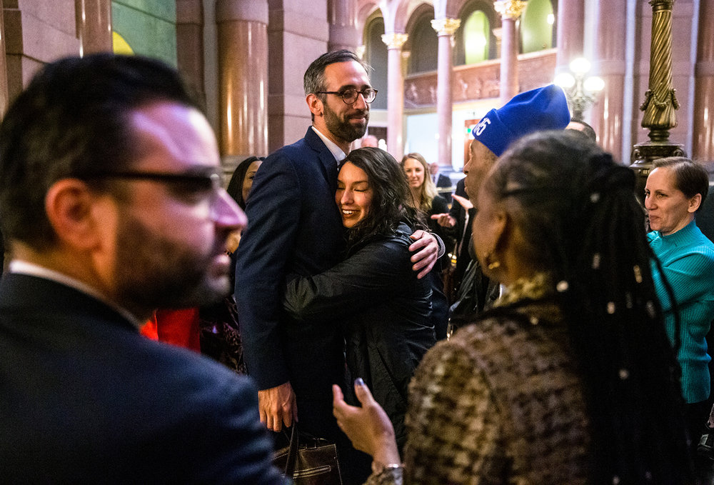 Illinois State Rep. Will Guzzardi, D-Chicago, center, gets a hug from Adriana Alvarez, of Chicago, Ill., as she joins supporters outside the Illinois House congratulating Guzzardi after Senate Bill 1, the bill to raise the minimum wage to $15 by 2025, passed the House with a vote of 69-47 at the Illinois State Capitol, Thursday, Feb. 14, 2019, in Springfield, Ill. [Justin L. Fowler/The State Journal-Register]
