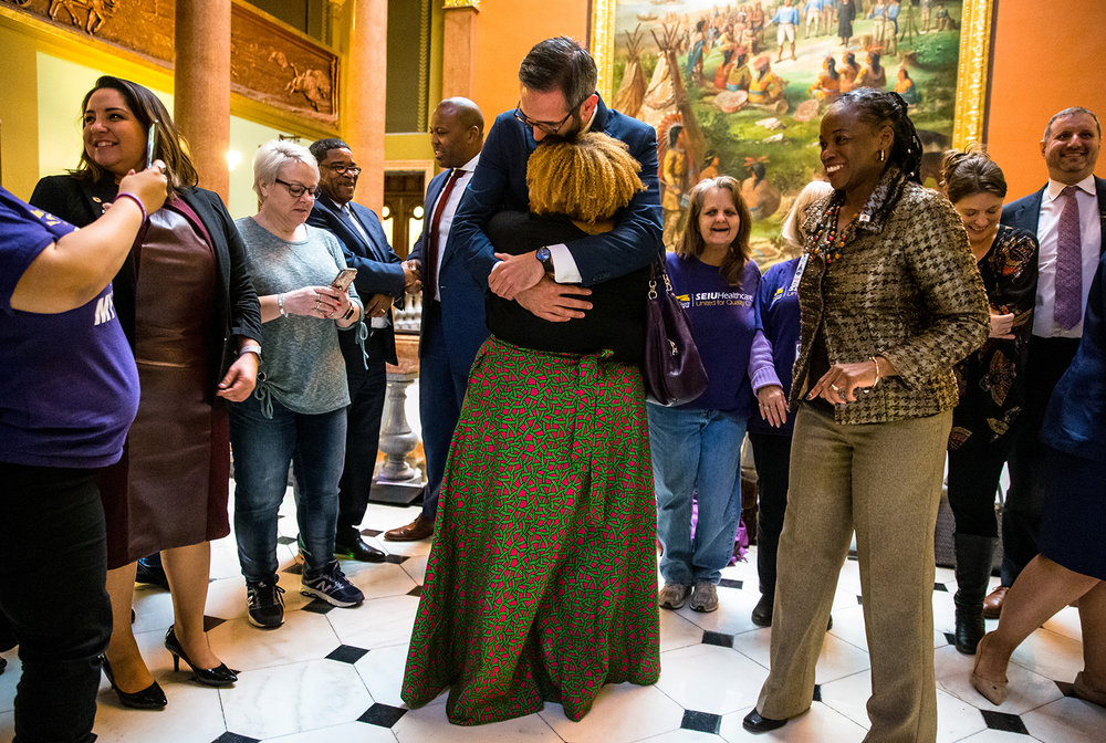 "Illinois State Rep. Will Guzzardi, D-Chicago, center, gets a an emotional hug from Erica Bland, of Chicago, Ill., as she joins supporters outside the Illinois House congratulating Guzzardi after Senate Bill 1, the bill to raise the minimum wage to $15 by 2025, passed the House with a vote of 69-47 at the Illinois State Capitol, Thursday, Feb. 14, 2019, in Springfield, Ill. ""I've been working on this bill with him for two years,"" said Bland. [Justin L. Fowler/The State Journal-Register]"