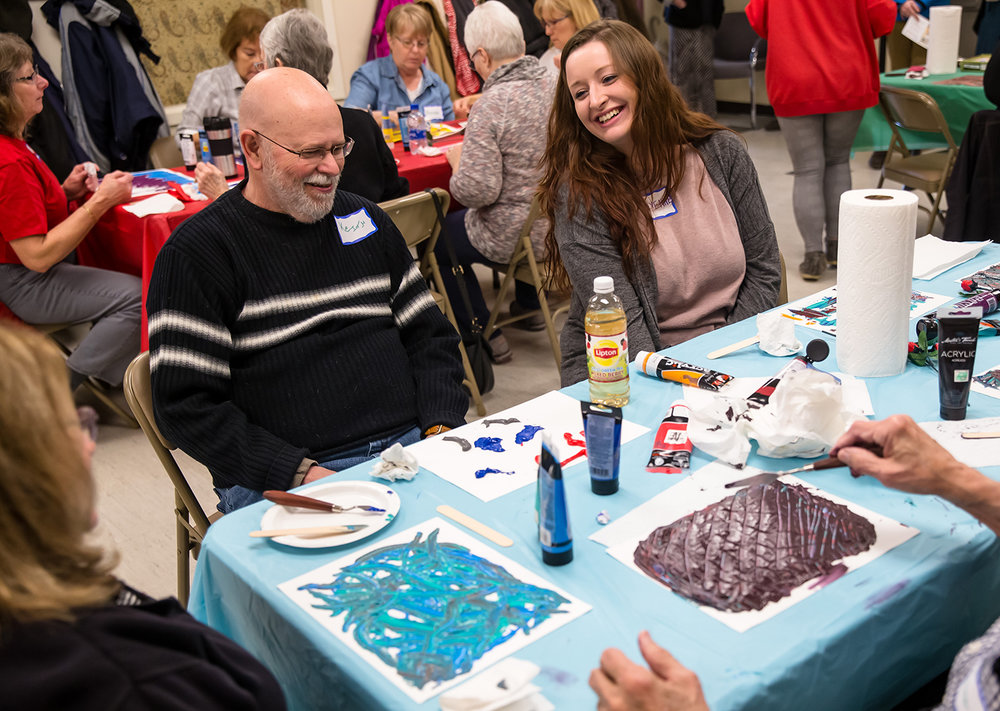 Cheyenne Snodgrass, center, a graduate student in University of Illinois Springfield Human Development Counseling Program, talks with Keith Kelley, left, about his abstract artwork project during the Art Express at Hope Presbyterian Church, Wednesday, Feb. 13, 2019, in Springfield, Ill. Individuals with memory loss and their care partners are finding a way to express their creativity through the Art Express class done through a partnership between the University of Illinois Springfield Human Development Counseling Program and the Southern Illinois University School of Medicine's Center for Alzheimer's Disease and Related Disorders. [Justin L. Fowler/The State Journal-Register]