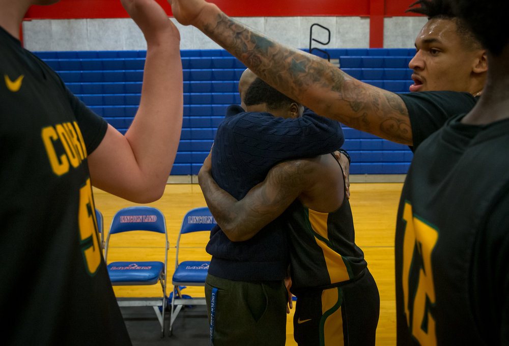 Parkland College's Yaakema Rose Jr. (1) gets a hug from Lincoln Land Community College men's basketball head coach Chuck Shanklin after the Cobras defeated the Loggers 91-59 at Lincoln Land Community College's Cass Gymnasium, Wednesday, Feb. 20, 2019, in Springfield, Ill. [Justin L. Fowler/The State Journal-Register]