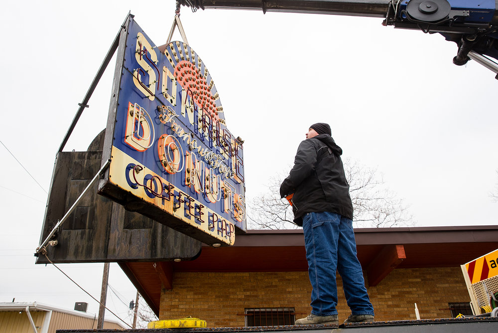 Jim McGlothlin with Ace Sign Company lowers the 6-by-8 foot neon and porcelain Sonrise Donuts sign off the building at 1101 S. Ninth St. where it has been for nearly 70 years Monday, Feb. 18, 2019. The local landmark, recently purchased by the City of Springfield, will be restored by the company and incorporated into the city's tourism efforts. [Ted Schurter/The State Journal-Register]