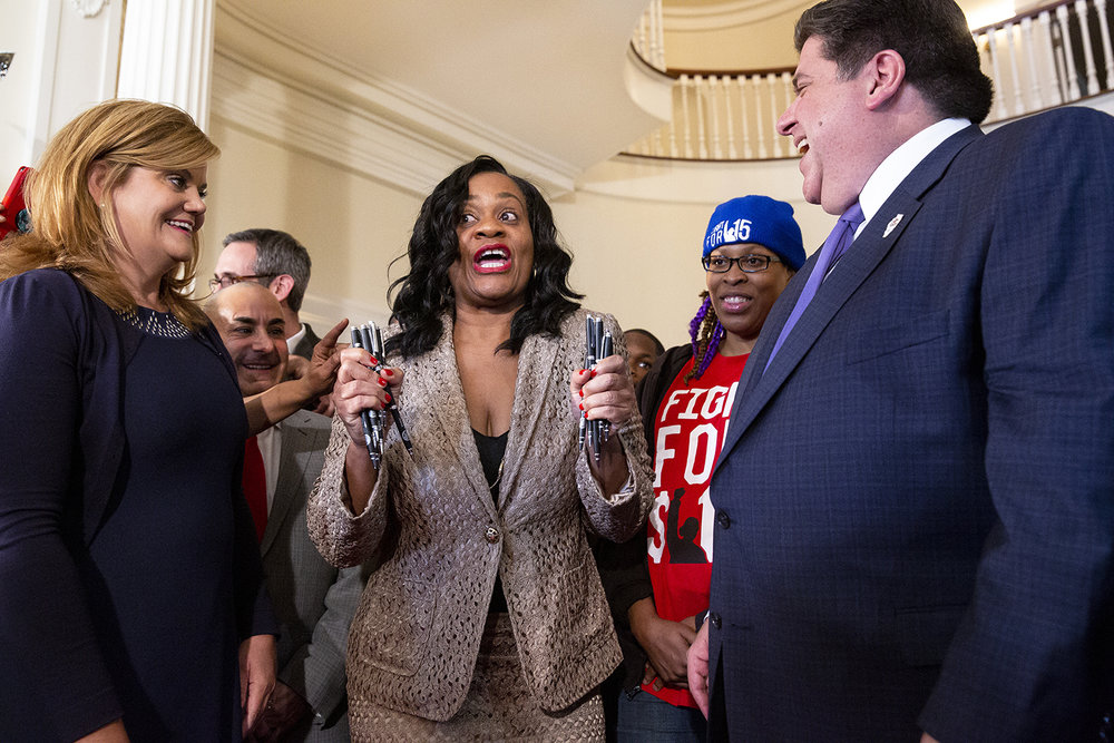 Sen. Kimberly Lightford, D-Maywood, had the task of handing out the pens Gov. J.B. Pritzker used after he signed SB1 into law during a ceremony Tuesday, Feb. 19, 2019 at the Executive Mansion in Springfield, Ill. The bill, which raises the minimum wage in Illinois, was championed by Lightford. [Rich Saal/The State Journal-Register]