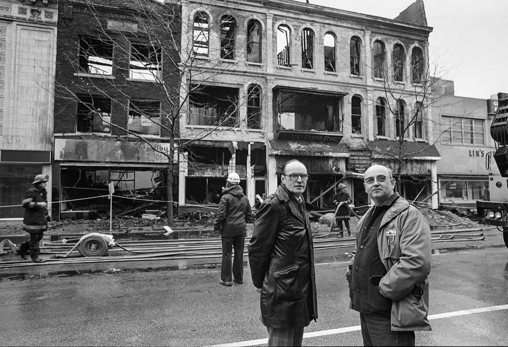 """Fire destroys several downtown buildings at the intersection of Fifth and Monroe streets, including the Herbert Georg photography studio at 217 1/2 S. Fifth St., Feb. 19, 1980. The studio owners, Kenneth Carroll, left, and Don Ewing, at the scene of the fire. Photos by Chris Covatta and Bill Hagen (aftermath and cleanup) File/The State Journal-RegisterPublished Feb. 20 - 24, 1980.Published as Picturing the Past March 3, 2019.People often say that if their home was destroyed by fire, the thing they would miss most are family photographs. A house or furnishings destroyed can be remedied, but losing irreplaceable images of lost loved ones would be heartbreaking. When fire broke out in the evening of Feb. 19, 1980, destroying several buildings on the northeast corner of Fifth and Monroe streets, it wasn't the material damage that stung the most. The vast, and valuable, collection of photographs contained in the Herbert Georg photography studio was a stunning loss of historical Springfield images dating to the 1920s.The studio was founded by Herbert Georg's father, Victor, and a partner in 1897. Victor was an early adopter of moving pictures and had filmed Charles Lindbergh piloting the first air mail plane to the city. That historic moment was just one of the gems destroyed in the fire.Gone were as many as 500,000 photographic negatives, movie films and the studio's unique photographic equipment. Because Georg used large format cameras creating 8x10 inch film negatives, the collection contained views of our city growing up in vivid, crystal clear detail.The studio recorded lots of firsts; the first air mail run to the city, the first cars on newly paved cobblestone streets, the first electric signs, as well as celebrity visitors and ordinary citizens.Herbert Georg died in 1964 and the studio was purchased by Kenneth Carroll and Don Ewing, above, who were on the scene of the fire contemplating the loss. """"Right after the fire, I was standing in the str"""