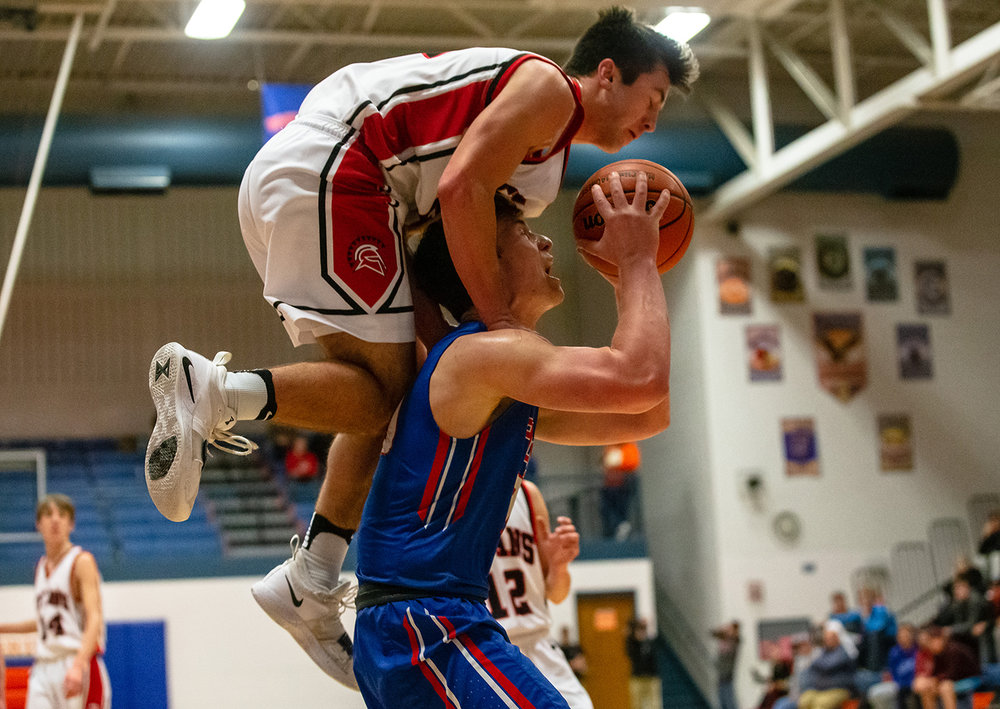 Pleasant Plains' Joel Niermann (30) is fouled by West Hancock's Peyton Dooley (22) climbing up on his shoulders as goes up for a shot after a rebound in the first half during the Class 2A Riverton Sectional Semifinals at the Hawk Center, Wednesday, Feb. 27, 2019, in Riverton, Ill. [Justin L. Fowler/The State Journal-Register]
