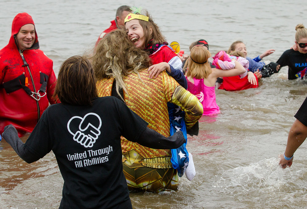 Taylor Patterson, a fifth grader at Pleasant Plains Middle School with Cerebral Palsy, smiles as she is carried into the frigid waters of Lake Springfield by Pleasant Plains Middle School principal Ben Theilen during the 2019 Polar Plunge benefiting the Special Olympics Illinois on Lake Springfield at the Knights of Columbus Lake Club Saturday, March 2, 2019. [Ted Schurter/The State Journal-Register]