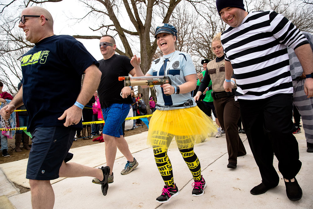 "Jamie Bramblett, center, runs toward the water with the ""Springfield Police and Friends"" team during the 2019 Polar Plunge benefiting the Special Olympics Illinois on Lake Springfield at the Knights of Columbus Lake Club Saturday, March 2, 2019. [Ted Schurter/The State Journal-Register]"