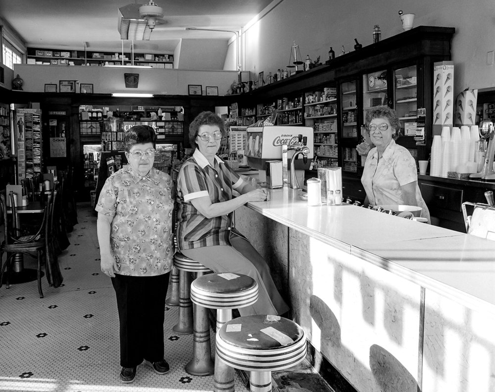 """Bachman and Keefner soda fountain at Sixth Street and Capitol Avenue March 27, 1986, photographed for Heartland Magazine feature pub. March 27, 1986. Jean Prather, left, Millie Yoakum and Mary Morris serve lunch and beverages. [Rich Saal/The State Journal-Register]Scanned Feb. 12, 2019.When Bachman and Keefner Prescription Druggists at the corner of Sixth Street and Capitol Avenue was open for business, Jean Prather, left, Millie Yoakum and Mary Morris ran the lunch counter and soda fountain, and they had a routine. Before the doors opened each morning for breakfast, the three had placed 11 coffee cups and saucers on the counter, one at each of the bright red stools. The coffee was ready to pour when the regulars walked in and took their (unofficially) reserved seats; the ladies already familiar with everyone's preferences. """"Sometimes a foreigner will jump in, especially in the summer,"""" Morris joked in a feature story published in The State Journal-Register in March 1986, acknowledging that a visitor would have no reason to know of the unwritten rule about stool entitlement. Morris went to work behind the counter at the drug store in 1941 when she was 17 and fresh out of Sacred Heart Academy. She was the first girl employed there. """"I was young and could bully the boys into helping."""" From her years of experience behind the counter, she had accumulated several celebrity sitings. Nelson Eddy, the actor and singer popular during the 1930s and 40s, would always stop by when he was in Springfield. Andy Williams, too. She also met the Three Stooges, and the Osmond family. """"Donny was a little bitty thing."""" In addition to being a full service pharmacy, the lunch counter was well known for its root beer floats and chocolate malts. On Thursdays, Morris would serve her olive-nut sandwiches made of ground peanuts, sliced green olives and mayonnaise. """"You either like them or you don't,"""" Morris said, """"some people only come in here on Thursdays."""" Bachman"""