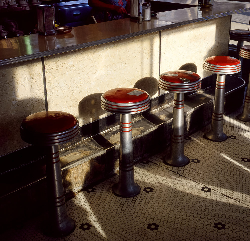 """Bachman and Keefner soda fountain at Sixth Street and Capitol Avenue March 27, 1986, photographed for Heartland Magazine feature pub. March 27, 1986. [Rich Saal/The State Journal-Register]Scanned Feb. 12, 2019.Published as Picturing the Past March 10, 2019When Bachman and Keefner Prescription Druggists at the corner of Sixth Street and Capitol Avenue was open for business, Jean Prather, left, Millie Yoakum and Mary Morris ran the lunch counter and soda fountain, and they had a routine. Before the doors opened each morning for breakfast, the three had placed 11 coffee cups and saucers on the counter, one at each of the bright red stools. The coffee was ready to pour when the regulars walked in and took their (unofficially) reserved seats; the ladies already familiar with everyone's preferences. """"Sometimes a foreigner will jump in, especially in the summer,"""" Morris joked in a feature story published in The State Journal-Register in March 1986, acknowledging that a visitor would have no reason to know of the unwritten rule about stool entitlement. Morris went to work behind the counter at the drug store in 1941 when she was 17 and fresh out of Sacred Heart Academy. She was the first girl employed there. """"I was young and could bully the boys into helping."""" From her years of experience behind the counter, she had accumulated several celebrity sitings. Nelson Eddy, the actor and singer popular during the 1930s and 40s, would always stop by when he was in Springfield. Andy Williams, too. She also met the Three Stooges, and the Osmond family. """"Donny was a little bitty thing."""" In addition to being a full service pharmacy, the lunch counter was well known for its root beer floats and chocolate malts. On Thursdays, Morris would serve her olive-nut sandwiches made of ground peanuts, sliced green olives and mayonnaise. """"You either like them or you don't,"""" Morris said, """"some people only come in here on Thursdays."""" Bachman and Keefner, which opened in"""