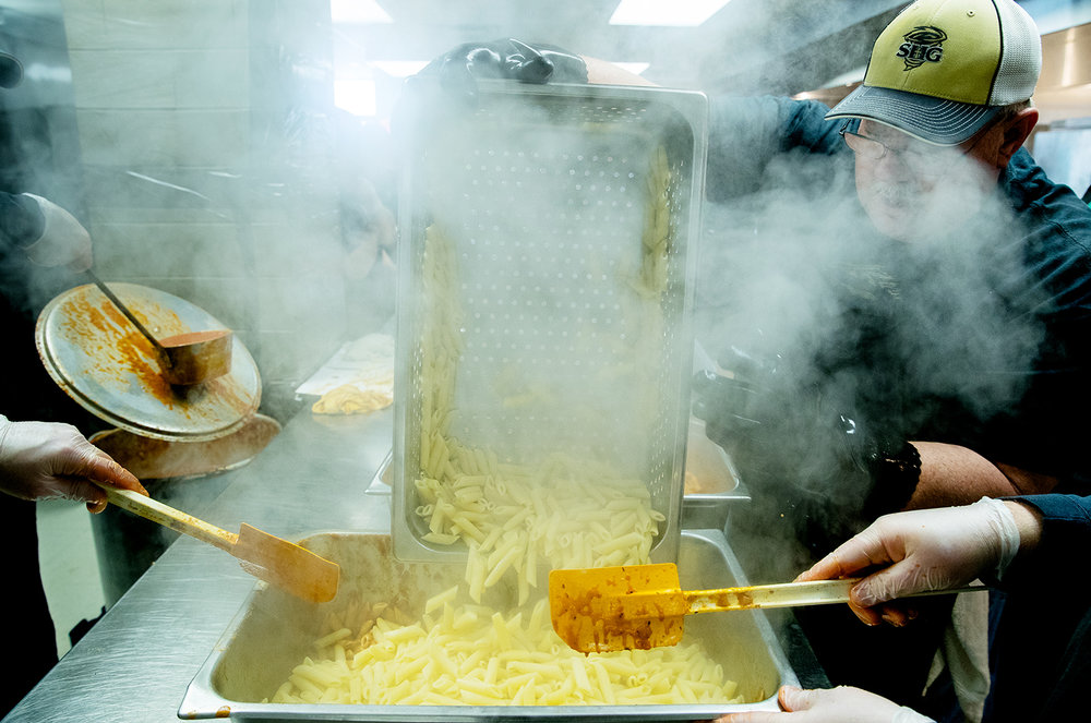 Brian Rhodes pours delivers a fresh pan of hot mostaccioli noodles to the sauce team during the 60th annual mostaccioli dinner at Sacred Heart-Griffin High School Sunday, March 3, 2019. [Ted Schurter/The State Journal-Register]
