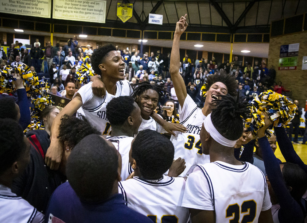 Southeast's James Dent (15), Terrion Murdix (4) and Michael Tyler (34) celebrate with the Spartans after they defeated Lincoln 66-43 in the Boys Class 3A Springfield Sectional championship at Herb Scheffler Gymnasium, Friday, March 8, 2019, in Springfield, Ill. [Justin L. Fowler/The State Journal-Register]