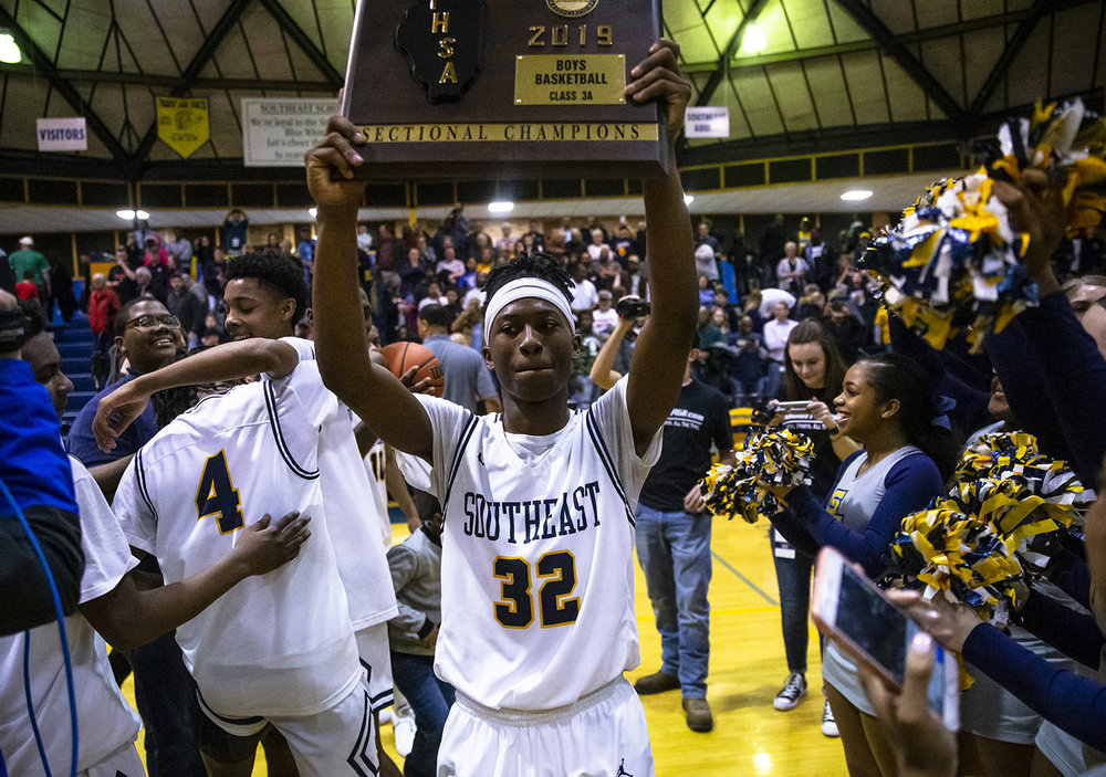 Southeast's Stepheon Sims (32) hoists up the championship plaque as the Spartans celebrate defeating Lincoln 66-43 in the Boys Class 3A Springfield Sectional championship at Herb Scheffler Gymnasium, Friday, March 8, 2019, in Springfield, Ill. [Justin L. Fowler/The State Journal-Register]