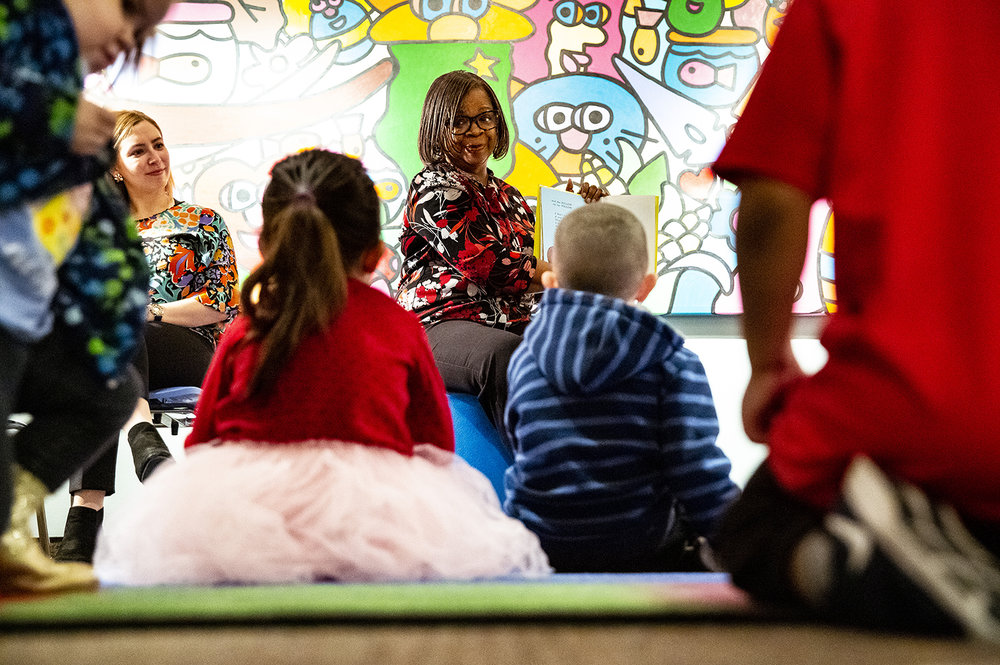 """Sidney Revetes, a Bank of Springfield employee, reads from the Dr. Seuss classic """"Wocket in my Pocket"""" during the Illinois State Museum's monthly Story Time program for preschool-age children Tuesday, March 12, 2019 in Springfield, Ill. Revetes was joined by two other BOS employees, including Kari Kelly, left, for a celebration in honor of Theodor Seuss Geisel, known to millions as Dr. Seuss, who would have been 115 years-old his month. BOS sponsors the museum's Story Time and Super Saturdays programs. [Rich Saal/The State Journal-Register]"""