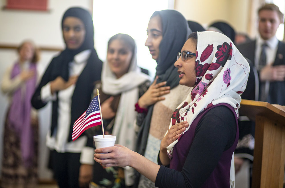 Fatina Faizal, 15, is joined with her fellow members of the Muslim Teenage Girls Group as they lead the room in the Pledge of Allegiance during a vigil of solidarity & support for the Islamic community and the New Zealand shooting victims hosted by the Greater Springfield Interfaith Association and the Islamic Society Of Greater Springfield at the Islamic Society of Greater Springfield mosque, Sunday, March 17, 2019, in Springfield, Ill. [Justin L. Fowler/The State Journal-Register]