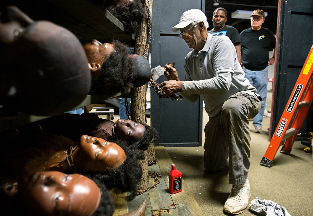"Jim Betts adds a bit of blood to a prop for an interactive audio-visual experience titled ""The Door of No Return"" at the The Springfield and Central Illinois African American History Museum Tuesday, March 19, 2019. Betts, an instructor in the Lincoln Land Community College highway construction careers program and retired Scenic Department Head at Paramount Studios, and a few LLCC students, created a 10 by 15 foot space meant to evoke the last door Africans would have passed through on their way to the hold of a slave ship. The exhibit opens March 23, at 5:30 p.m. and will also include narratives on the history of slavery and the Middle Passage. [Ted Schurter/The State Journal-Register]"