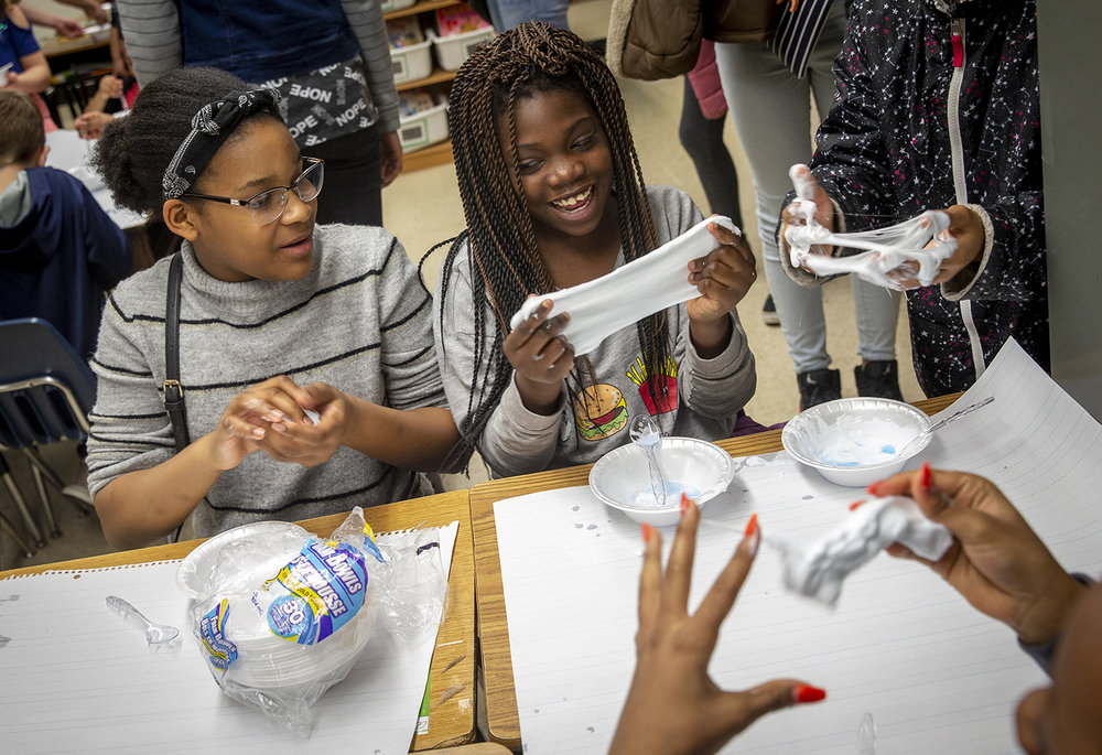 "Rakeya Amos, 10, center, shows how mixing glue and laundry detergent together created a version of ""slime"" to her classmate Aniyah Rhinehouse, 11, left, during Science and Math Night at Hazel Dell Elementary School, Thursday, March 21, 2019, in Springfield, Ill. The program was for Hazel Dell students and their families and gave them opportunities to learn about math and science through hands on activities. [Justin L. Fowler/The State Journal-Register]"
