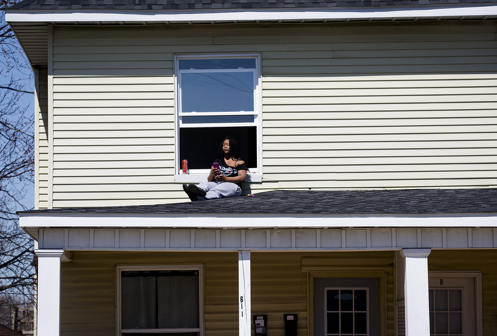Chantel McDonald soaks up the afternoon sun and fresh air from the porch roof of her apartment on West Washington Street Tuesday, March 26, 2019, in Springfield, Ill. According the the National Weather Service, high temperatures will be in the 60s through Friday, with a chance of rain. [Rich Saal/The State Journal-Register]