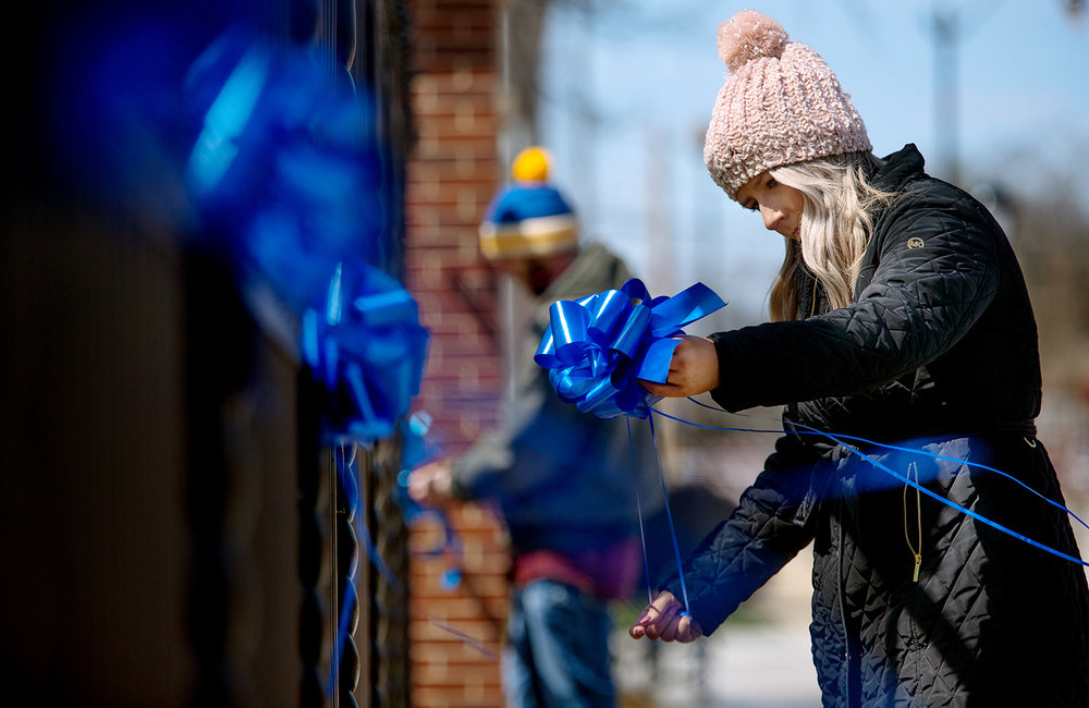 Melissa Christian ties blue ribbons onto the fence of the Illinois Executive Mansion Monday, April 1, 2019. Christian was volunteering with Prevent Child Abuse Illinois to help commemorate April as National Child Abuse Prevention Month. Nearly 600 ribbons and 75 bows were secured to the fence. [Ted Schurter/The State Journal-Register]