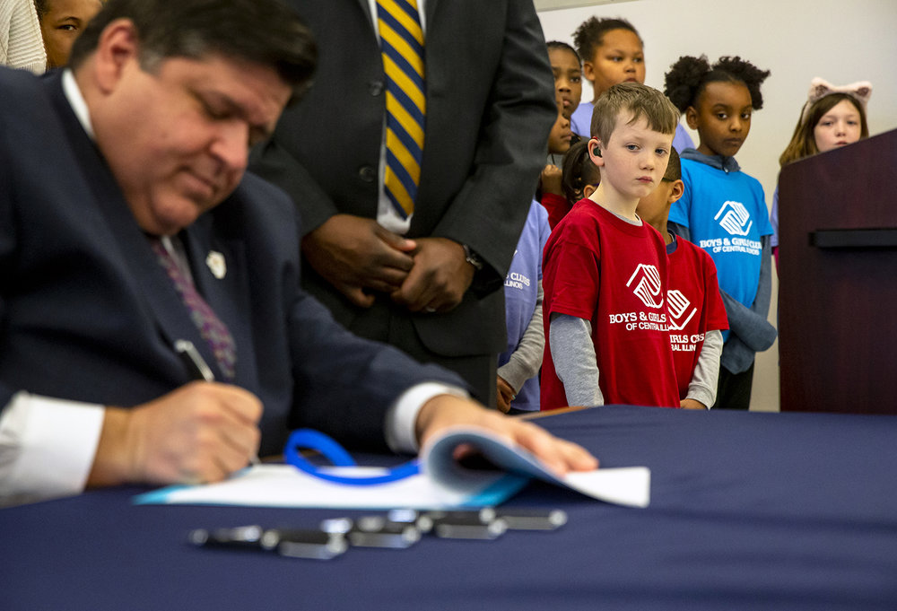 Emmett Tavender, 7, center, Sydney Williams, 9, and Abby Tavender, 10, right, join with members of the Boys and Girls Clubs of Central Illinois as they watch Illinois Governor J.B. Pritzker sign HB 2505, a bill allowing universities to retain unused AIM HIGH scholarship funds and allow for flexibility administering the program, during a press conference at Southeast High School, Thursday, April 4, 2019, in Springfield, Ill. [Justin L. Fowler/The State Journal-Register]
