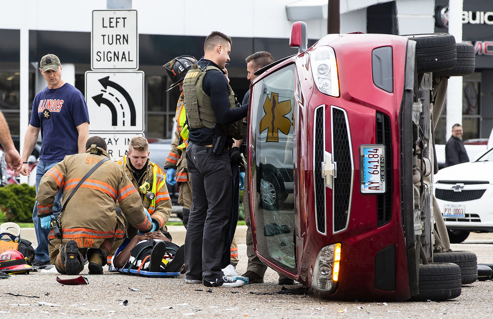 Springfield firefighters attend to a person injured in a rollover accident involving two vehicles at the intersection of Dirksen Parkway and South Grand Avenue, Tuesday, April 23, 2019, in Springfield, Ill. The vehicle, which had two occupants, had refused to pull over on a traffic stop from the Sangamon County Sheriff's DIRT Team at sped off at a high rate of sped, but was't pursued but the Sheriff's office. Springfield Police located the vehicle after finding it involved in the accident and the two occupants were transported to Memorial Medical Center with non-life threatening injures. [Justin L. Fowler/The State Journal-Register]