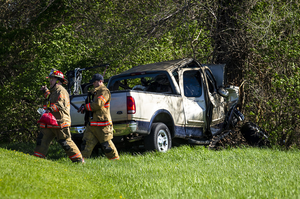 Springfield firefighters secure the scene of a single vehicle accident involving a pickup truck that collided with a tree head on just south of the intersection of 11th Street and University Drive near the University of Illinois Springfield, Friday, April 26, 2019, in Springfield, Ill. The drive of the vehicle was transported the hospital. [Justin L. Fowler/The State Journal-Register]