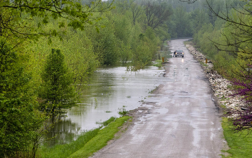 Water encroaches toppling over a section of Young Road as recents rains have caused flooding from the Sangamon River, Thursday, May 2, 2019, near Rochester, Ill. [Justin L. Fowler/The State Journal-Register]