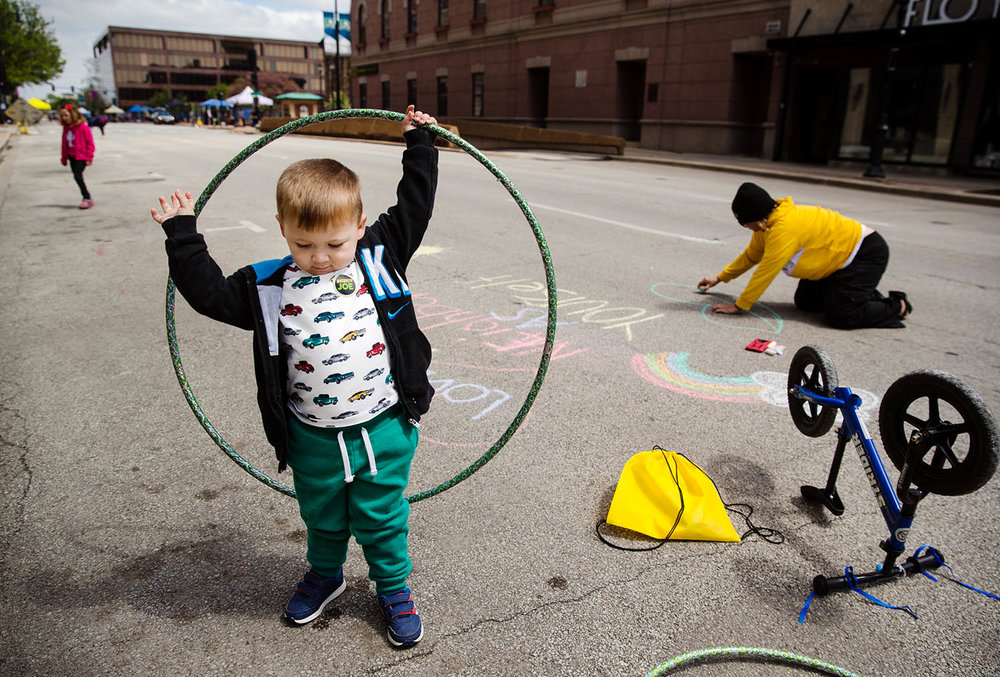 Josiah Guzouskis plays with a hula hoop as his mom Christy Painter creates chart artwork on Fifth Street during the Downtown Open Streets event Saturday, May 4, 2019. Participants could ride bikes, scooters, walk, run or jog and partake in organized fitness activities without worrying about automobile traffic. [Ted Schurter/The State Journal-Register]