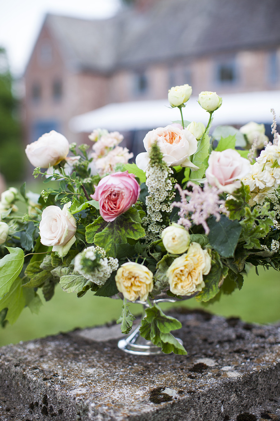 SYBIL - Reminiscent of an English garden, our Sybil arrangements are filled with European elegance and a touch of whimsy.  Your package includes florals designed in a compote (choose gold or silver), votives (choose gold, silver, or clear), and seasonal blooms.