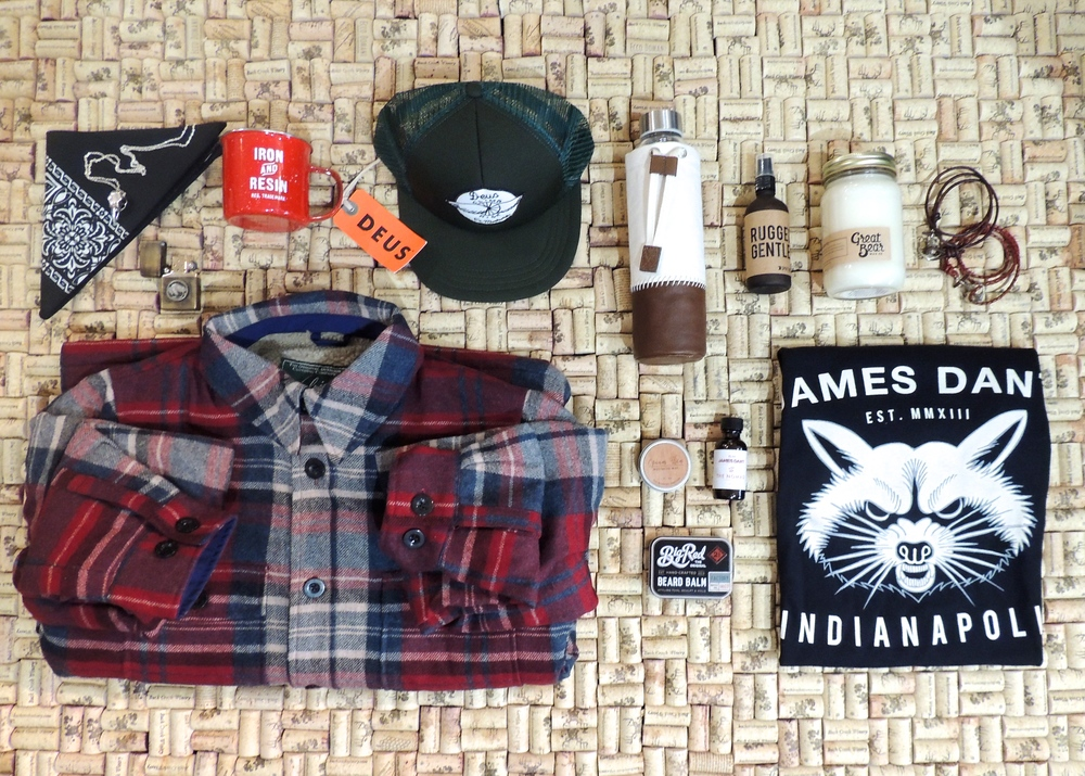 From top left to bottom right:Bandana,Hudson Made $6 | Necklace,Sparksmith Ark Industries $46 | Lighter,Silver Piston $95 | Mug,Iron and Resin $15 | Trucker Hat,Deus Ex Machina $29 | Lined Flannel,oolrich $189 | Waterbottle,Alternative $20 | Body Spray,Happy Spritz $28 | Mustache Wax,Bearded Bastard $15-18 | Beard Oil,James Dant $28 | Beard Balm,Big Red Balm $28 | Candle,Great Bear Wax Co.$32 | Bracelets,Maritime Supply Co.$38-75 | T-shirt,James Dant $30