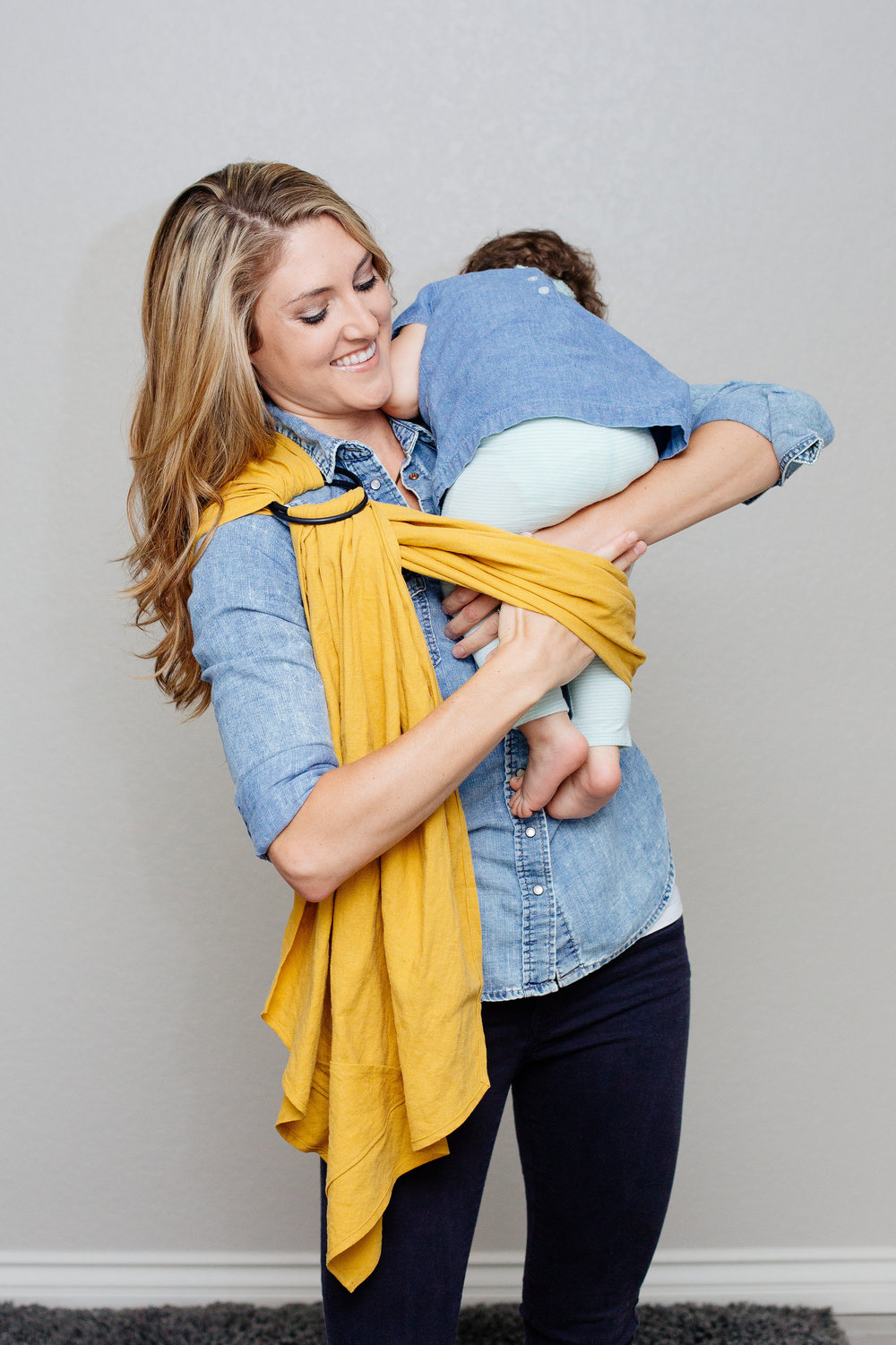 8 Place your baby high on your shoulder as if to burp them. Holding them with one hand, bring your other hand under the fabric loop to pull their legs through.