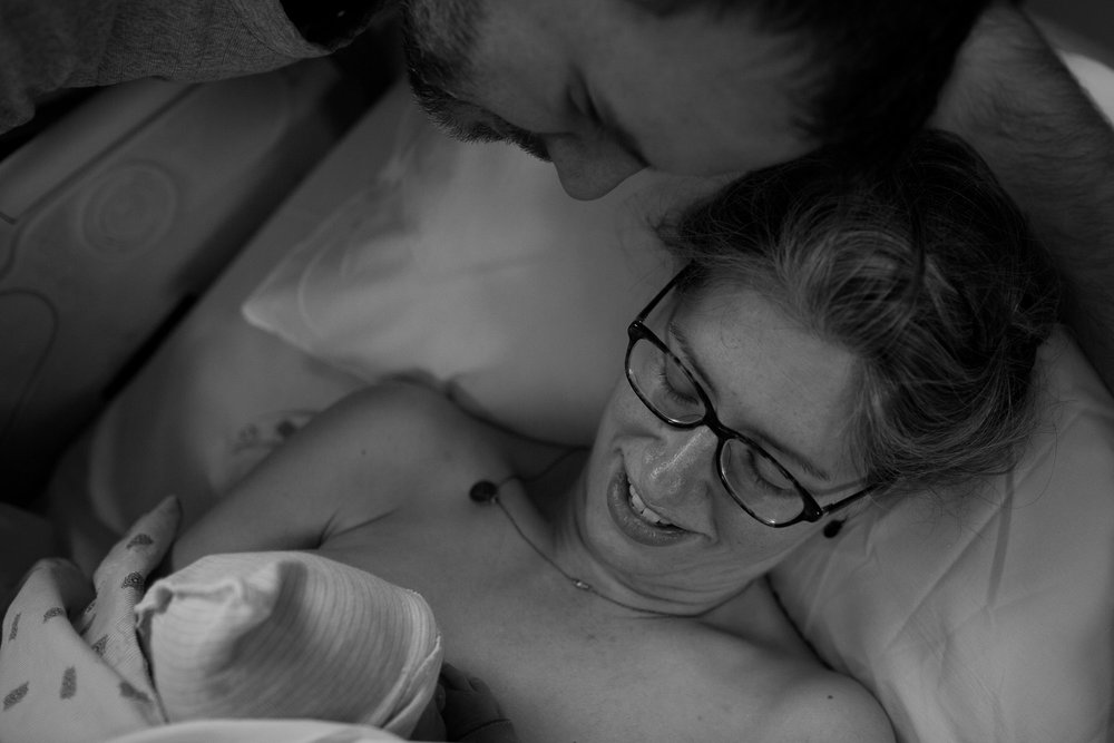 Skin to Skin with mommy, daddy looks on.  Austin birth photographer.  Birth photography.
