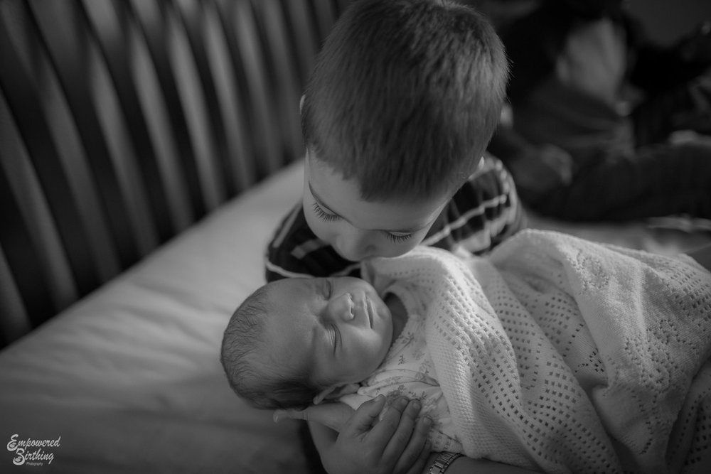 Big brother looks down lovingly o his baby sister.  Austin lifestyle newborn photography.