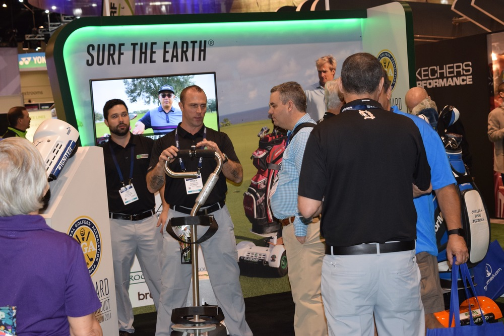 Brock Sabo demonstrates the GolfBoard to a captivated show patron while Cam Petriw looks on.
