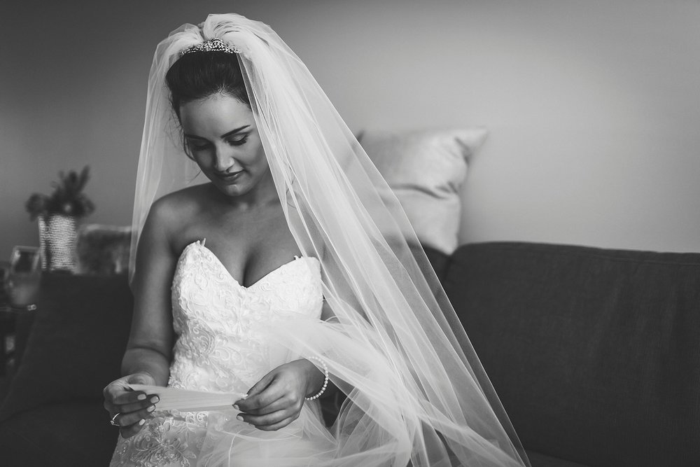 Bride in her Maggie Sottero wedding dress from the Model Shop reads a note from her groom before their St. John's, Newfoundland wedding.