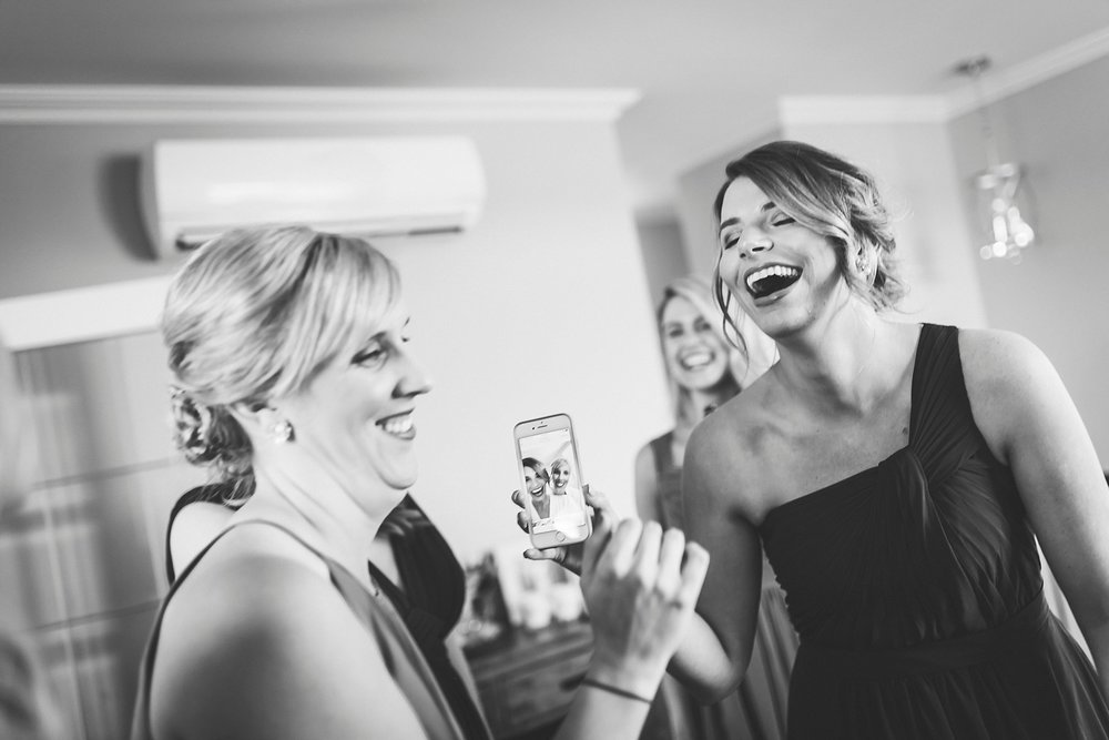 Bridesmaids laugh at a self on their phone before a St. John's, Newfoundland wedding