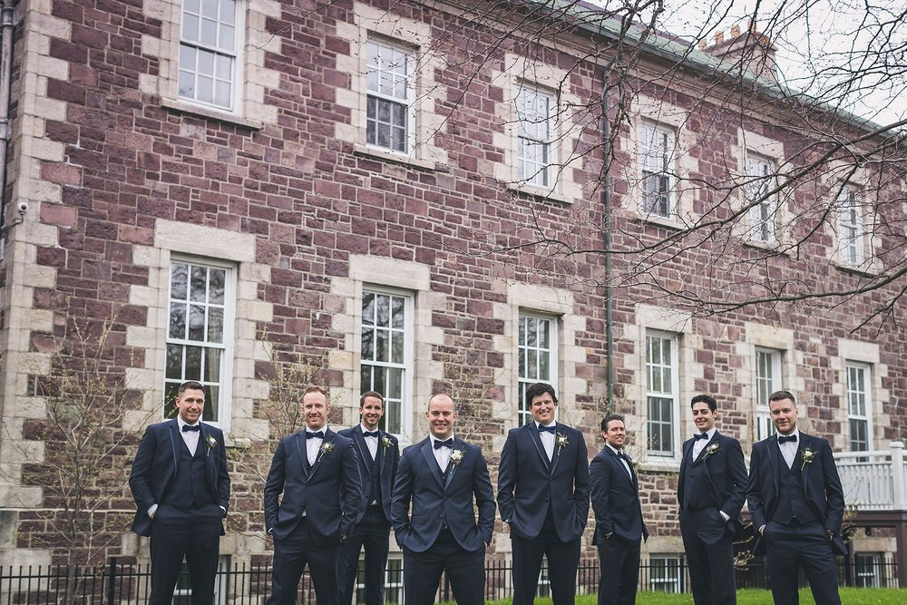 Groom and Groomsmen in suites from Moores Clothing for Men outside Government House during a St. John's, Newfoundland wedding