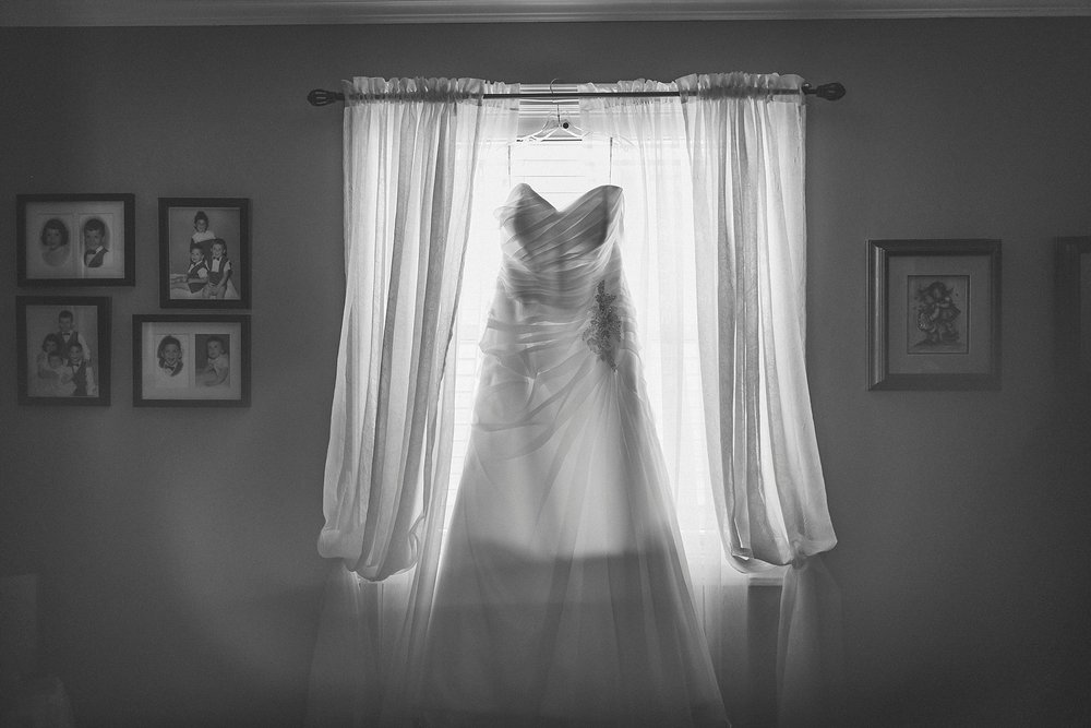 Bridal dress from Ever After Bridal Boutique hangs in a window before a Newfoundland wedding in St. John's