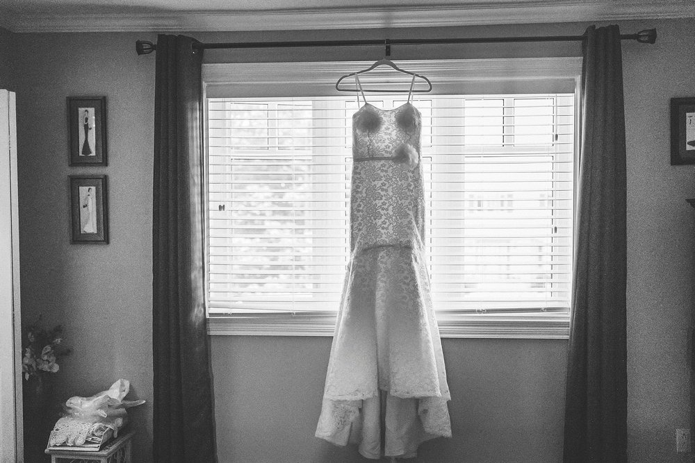 Mikaella bridal gown hangs in a window before a St. John's Wedding